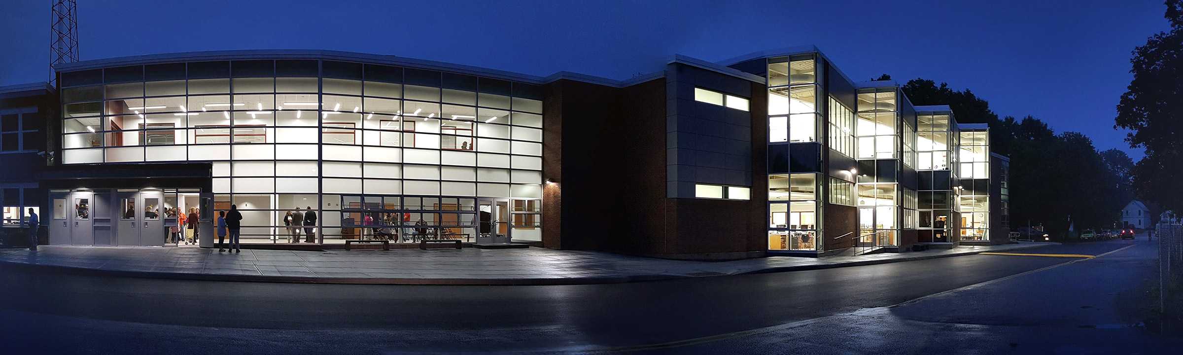 Panoramic photo of Burnt Hills-Ballston Lake High School building in the evening with brightly-lit windows and people