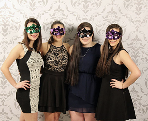 four students wearing formal dresses and masquerade masks