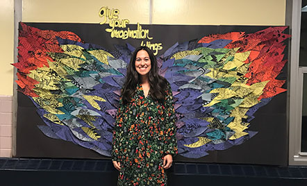 Teacher stands in front of wings display board