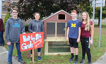 students standing next to chicken coop they helped build