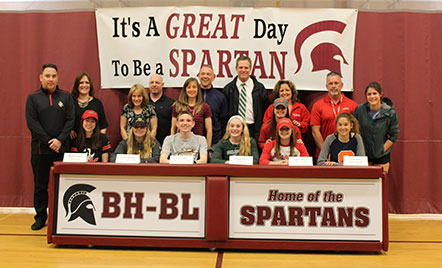 students and their parents sitting behind a table signing letters of intent