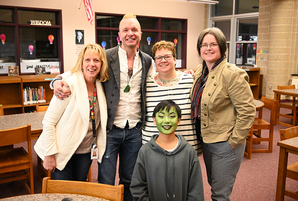 adults standing with student wearing green face makeup