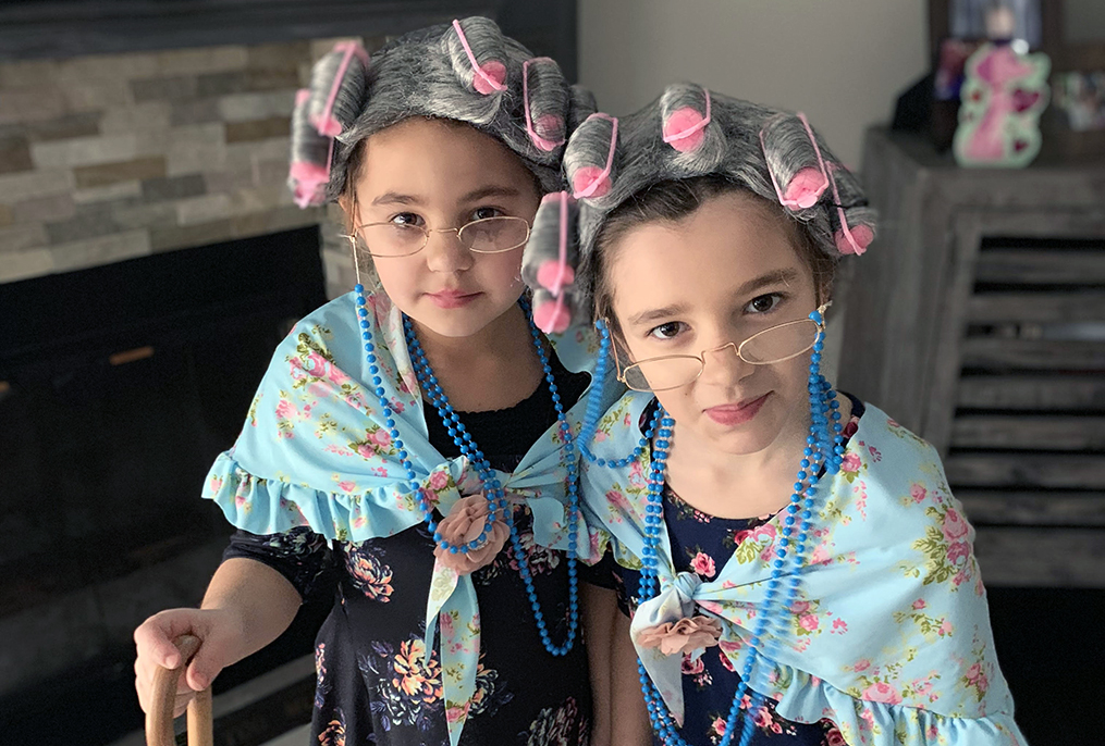 Two students pose with curlers in their hair, glasses and shawls for the 100th day of school