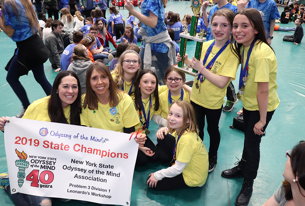 two adults and 6 students posing with winning trophy and championship sign
