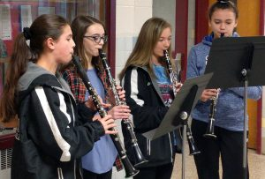 middle school students playing clarinets in hallway peformance