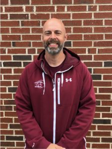coach in maroon sweatshirt