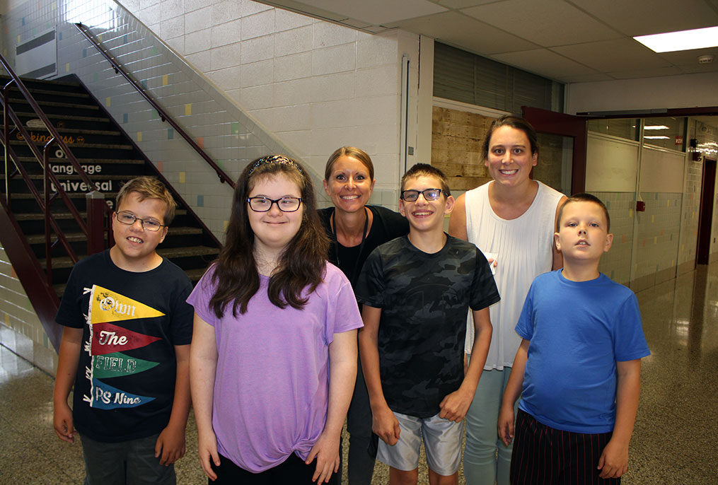 four students and two teachers standing together in a hallway