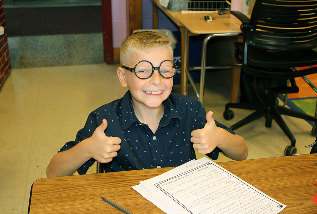 student giving two thumbs up and wearing Harry Potter glasses