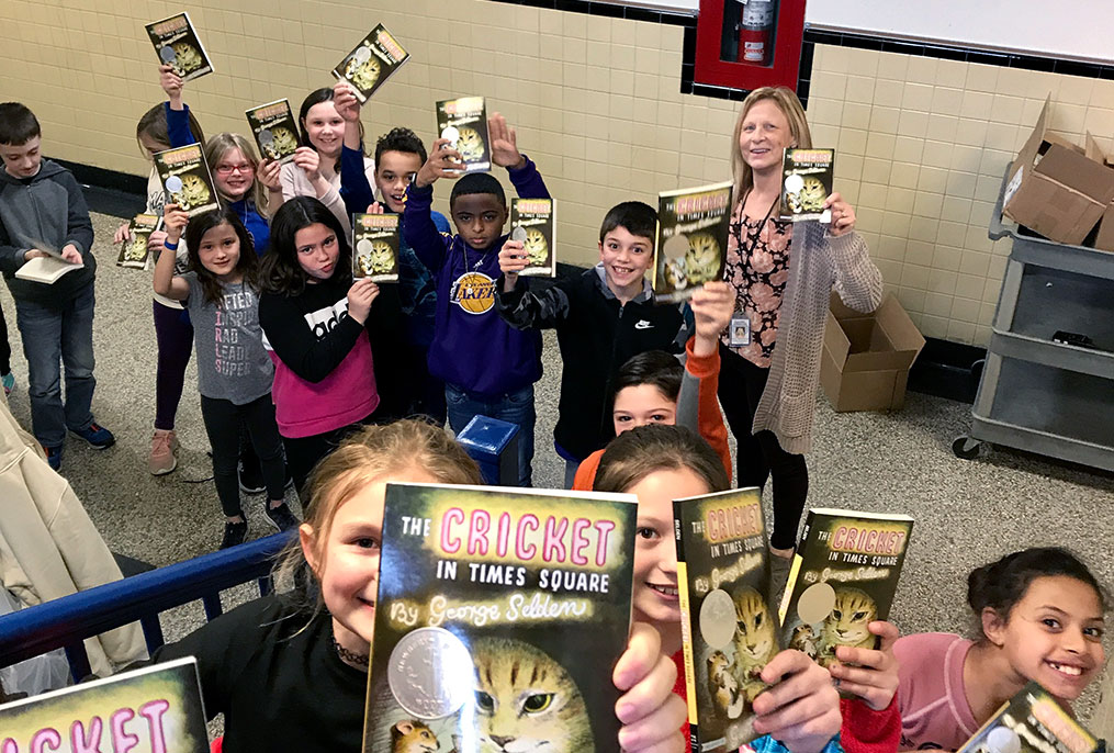 large group of elementary school students holding up the same book