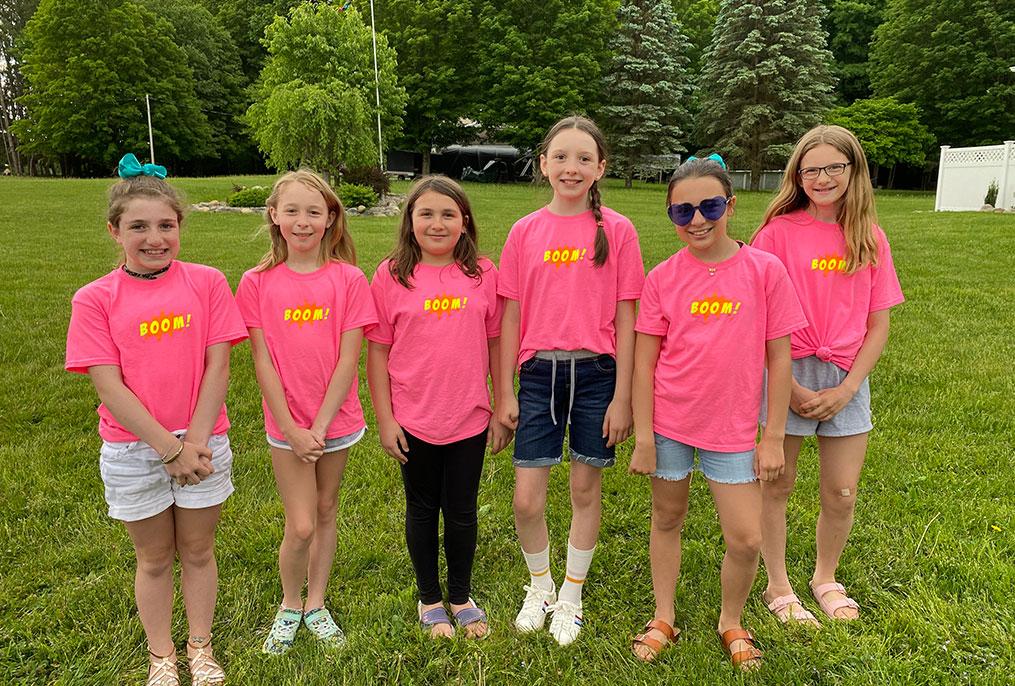 six students wearing bright pink shirts